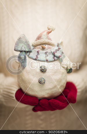 Woman Wearing Seasonal Red Mittens Holding Glass Snowman  stock photo, Woman Wearing A Sweater and Seasonal Red Mittens Holding An Ornate Glass Snowman. by Andy Dean