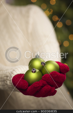 Woman Wearing Seasonal Red Mittens Holding Green Christmas Ornam stock photo, Woman Wearing A Sweater and Seasonal Red Mittens Holding Three Green Christmas Ornaments. by Andy Dean