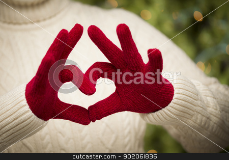 Woman Wearing Red Mittens Holding Out a Heart Hand Sign stock photo, Woman in Sweater with Seasonal Red Mittens Holding Out a Heart Sign with Her Hands. by Andy Dean