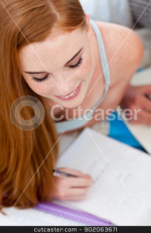 Beautiful teenager doing homework on the floor stock photo, Beautiful teenager doing homework on the floor with her friends by Wavebreak Media