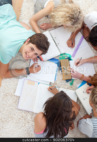 Group of Teenagers studying together stock photo, Group of Teenagers lying on the ground studying together by Wavebreak Media
