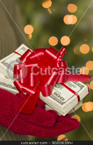 Woman Wearing Mittens Holding Stacks of Money with Red Ribbon stock photo, Woman Wearing Red Mittens and Green Sweater Holding Stacks of Hundreds of Dollars of Money with Red Ribbon. by Andy Dean