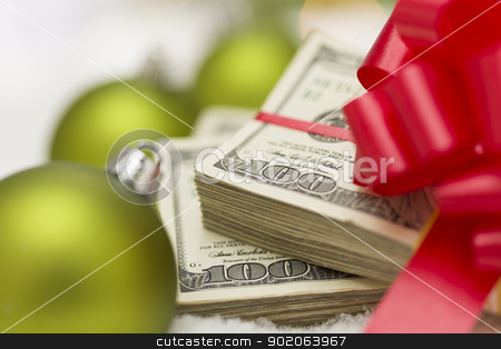 Stack of Hundred Dollar Bills with Bow Near Christmas Ornaments stock photo, Stack of One Hundred Dollar Bills with Red Bow Near Green Christmas Ornaments on Snow Flakes. by Andy Dean