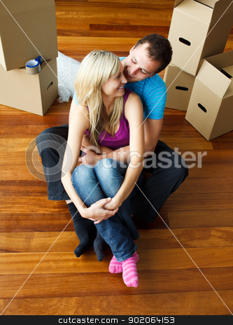 Happy young couple sitting on floor. Moving house stock photo, Happy young couple sitting on floor together. Moving house by Wavebreak Media