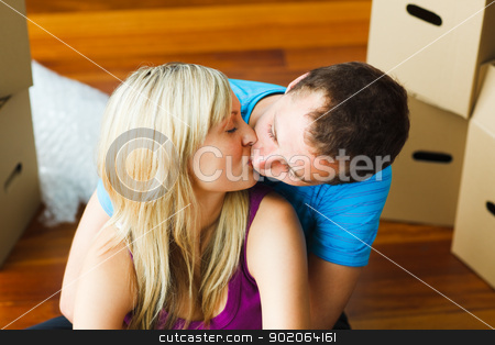 Couple moving to new house and kissing  stock photo, Happy couple moving to new house and kissing by Wavebreak Media