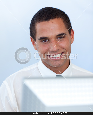 Smiling businessman working with a computer stock photo, Smiling businessman working with a computer in office by Wavebreak Media