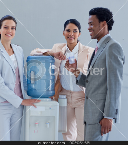Business people with a water cooler in office stock photo, Business people speaking next to a water cooler in office by Wavebreak Media