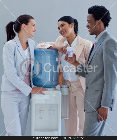 Business people speaking next to a water cooler stock photo, Business people speaking next to a water cooler in office by Wavebreak Media