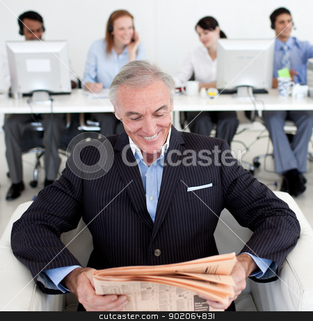 Smiling businessman reading a newspaper  stock photo, Smiling businessman reading a newspaper with his team in the background by Wavebreak Media