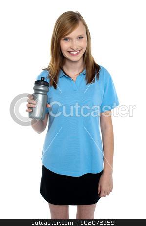 Teen in sports wear posing with a water bottle stock photo, Charming teen in sports wear posing with a water bottle. Refreshing drink. by Ishay Botbol