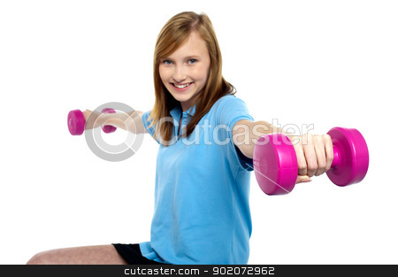 Cute young girl stretching dumbbells sideways stock photo, Cute young girl stretching dumbbells sideways. Exercising for fitness. by Ishay Botbol