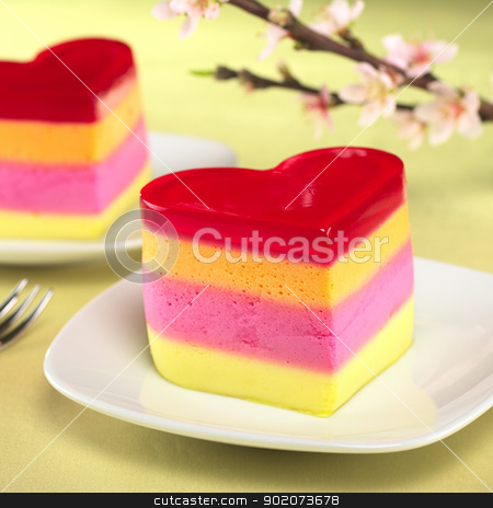 Peruvian Jelly Cake stock photo, Colorful Peruvian heart-shaped jelly-pudding cakes called Torta Helada with a blooming peach branch in the back (Selective Focus, Focus on the front of the first cake) by Ildi Papp