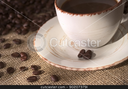 Coffee Bean stock photo, Coffee beans on the saucer of a coffee cup surrounded by many coffee beans on fabric called Jute (Very Shallow Depth of Field, Focus on the front coffee bean on the saucer and some on the fabric) by Ildi Papp