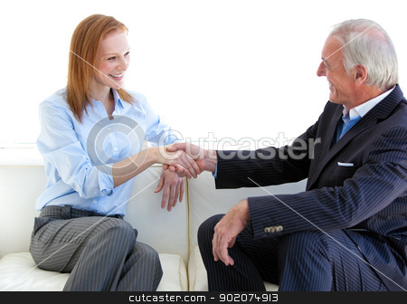 Smiling business people shaking hands sitting on a sofa stock photo, Smiling business people shaking hands sitting on a sofa in a modern building by Wavebreak Media