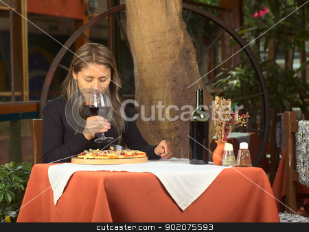 Young Peruvian Woman in Restaurant stock photo, Beautiful young Peruvian woman smelling her red wine with eyes closed and eating pizza in a restaurant  by Ildi Papp