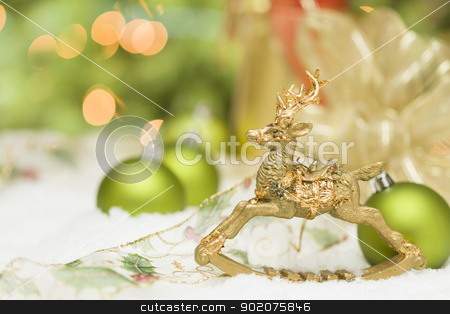 Golden Christmas Reindeer Ornament Among Snow, Bulbs and Ribbon stock photo, Beautiful Golden Christmas Reindeer Ornament Among Snow, Bulbs and Ribbon Against an Abstract Background. by Andy Dean