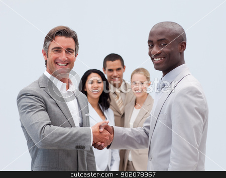 Caucasian and Afro-American businessmen shaking hands stock photo, Caucasian and Afro-American businessmen shaking hands with his colleagues in the background by Wavebreak Media