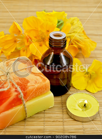 Oil with nasturtiums and candle stock photo, Oil in a bottle, two homemade soaps, nasturtium flowers, yellow candle on a bamboo mat by rezkrr