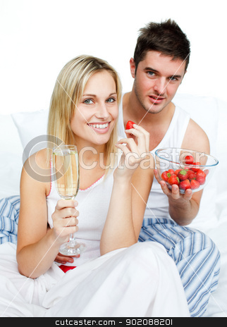 Couple celebrating an engagement with strawberries and champagne stock photo, Couple celebrating an engagement with strawberries and champagne in bed by Wavebreak Media