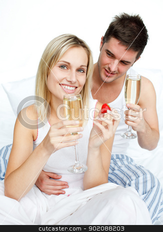 Couple eating strawberries and drinking champagne stock photo, Couple eating strawberries and drinking champagne in bed by Wavebreak Media