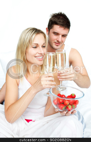 Couple toasting with champagne to an engagement  stock photo, Couple toasting with champagne to an engagement  in bed by Wavebreak Media