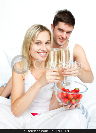 Couple toasting with champagne and strawberries to an engagement stock photo, Couple toasting with champagne and strawberries to an engagement  in bed by Wavebreak Media