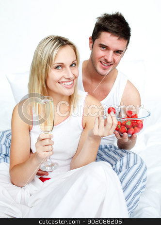 Loves eating strawberries and drinking champagne stock photo, Lovers eating strawberries and drinking champagne in bed by Wavebreak Media