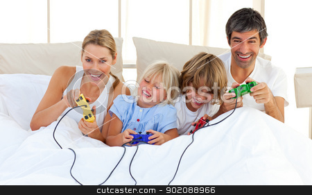 Adorable family playing video game in the bedroom stock photo, Adorable family playing video game lying on bed by Wavebreak Media