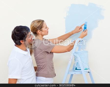 Happy couple painting together stock photo, Happy couple painting together in their new house by Wavebreak Media