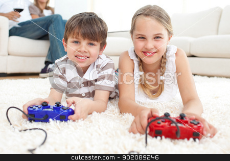 Cute brother and sister playing video games stock photo, Cute brother and sister playing video games lying on the floor by Wavebreak Media