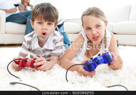 Animated children playing video games stock photo, Animated children playing video games lying on the floor by Wavebreak Media