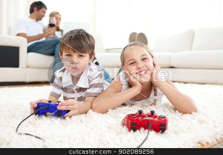 Adorable siblings playing video games stock photo, Adorable siblings playing video games lying on the floor by Wavebreak Media