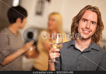 Smiling Young Man with Glass of Wine Socializing stock photo, Smiling Young Man with Glass of Wine Socializing in a Party Setting. by Andy Dean