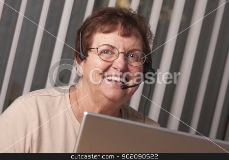 Smiling Senior Adult Woman with Telephone Headset and Monitor stock photo, Smiling Senior Adult Woman with Telephone Headset In Front of Computer Monitor. by Andy Dean