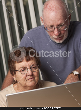 Smiling Senior Adult Couple Having Fun on the Computer stock photo, Smiling Senior Adult Couple Having Fun on the Computer Laptop Together. by Andy Dean