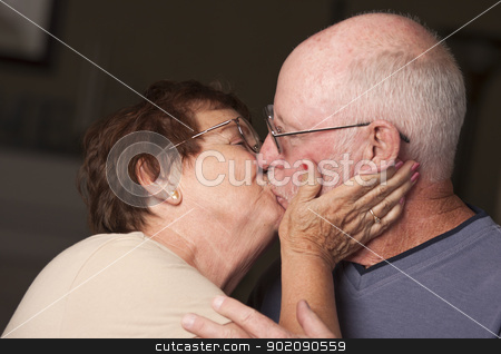Happy Senior Couple Kissing stock photo, Affectionate Happy Senior Couple Kissing. by Andy Dean