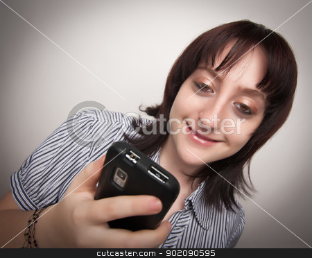 Smiling Brunette Woman Using Cell Phone stock photo, Smiling Brunette Woman Using Cell Phone on a Grey Background. by Andy Dean