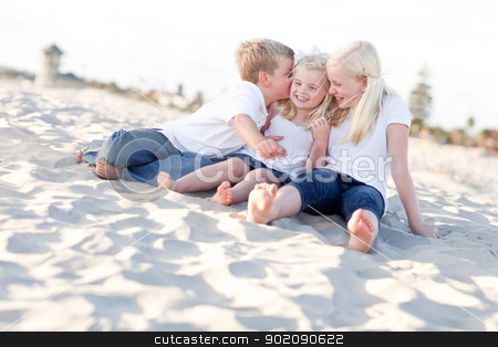 Adorable Sibling Children Kissing the Youngest stock photo, Adorable Sibling Children Kissing the Youngest at the Beach. by Andy Dean