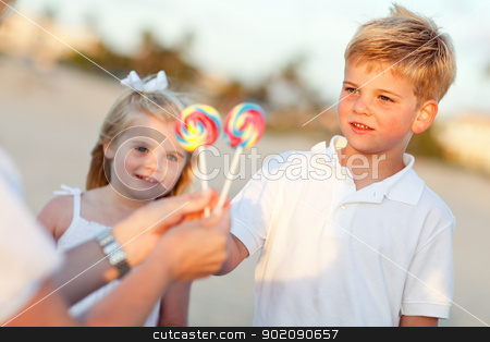 Cute Brother and Sister Picking out Lollipop stock photo, Cute Brother and Sister Picking out Lollipop from Their Mom at the Beach. by Andy Dean