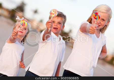 Cute Brother and Sisters Enjoying Their Lollipops Outside stock photo, Cute Brother and Sisters Enjoying Their Lollipops Outside at the Beach. by Andy Dean