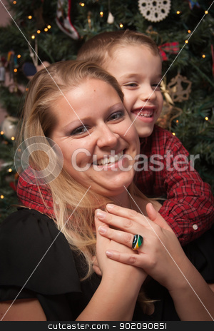Adorable Son Hugging His Mom in Front Of Christmas Tree stock photo, Adorable Son Hugging His Mom in Front Of Their Christmas Tree. by Andy Dean