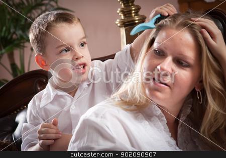 Cute Son Brushing His Mom's Hair stock photo, Cute Son Brushing His Mom's Hair Indoors. by Andy Dean