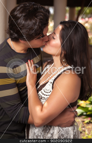 Attractive Hispanic Couple Kissing Outdoors stock photo, Attractive Hispanic Couple Kissing Outdoors in the Park. by Andy Dean