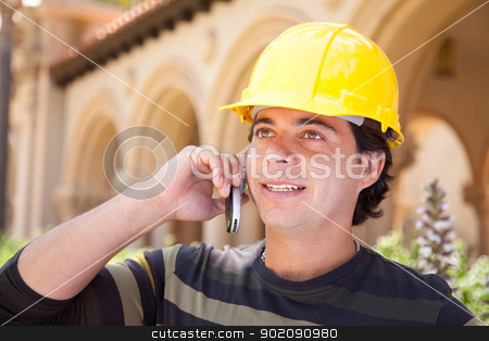 Handsome Hispanic Contractor on Phone with Hard Hat Outside stock photo, Handsome Hispanic Contractor with Hard Hat Talking on His Cell Phone. by Andy Dean