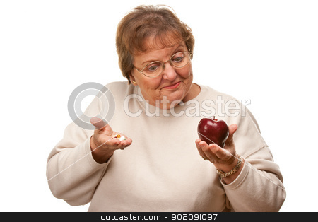 Confused Senior Woman Holding Apple and Vitamins stock photo, Confused Senior Woman Holding Apple and Vitamins Isolated on a White Background. by Andy Dean