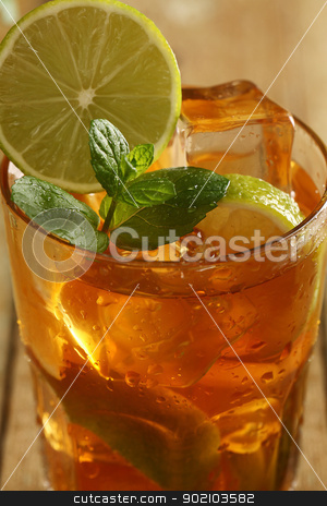 Fresh cold tea with lime, mint and lemon stock photo, Fresh cold tea with lime, mint and lemon on a wooden surface by yekostock