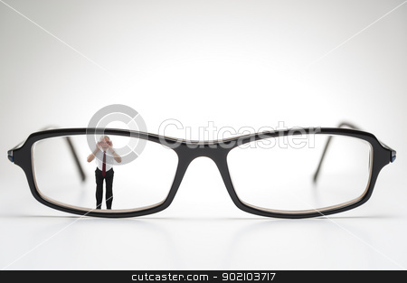 Diminutive elderly man peering through spectacles stock photo, Diminutive elderly man peering through a lens on a pair of spectacles or prescription glasses , a humorous take on aging eyesight requiring corrective glasses by Instudio 68