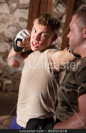 Fighter Throws Punches stock photo, Young fighter with mouthpiece throws punches at his opponent by Scott Griessel