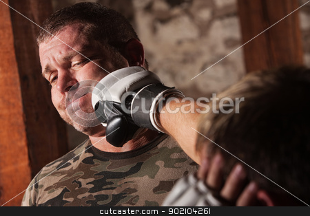 Fighter Gets Punched stock photo, Man in camouflage hit with a right punch by Scott Griessel