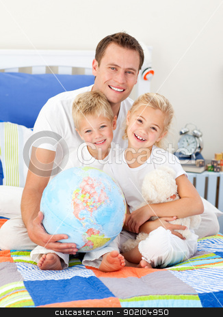 Cheerful father and his children holding a terretrial globe  stock photo, Cheerful father and his children holding a terretrial globe sitting on a bed by Wavebreak Media